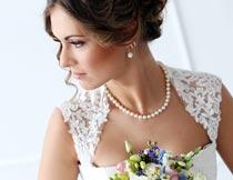 拿着鲜花戴珍珠项链的新娘摄影图片