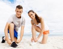海边沙滩上系鞋带的情侣摄影图片