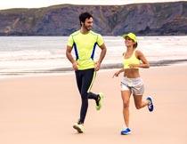 海边沙滩上跑步运动的情侣摄影图片