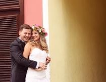 门前开心拥抱的婚纱新人摄影图片
