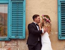 窗户前甜蜜拥抱的婚纱新人摄影图片