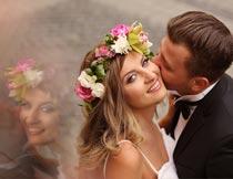 戴花环亲吻脸颊的甜蜜新人摄影图片