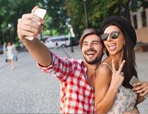 街道上手机开心自拍的情侣摄影图片