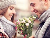 双手捧着花束对视的情侣摄影图片