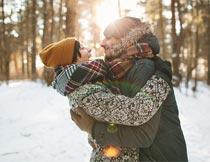 阳光下树林雪地拥抱的情侣摄影图片