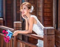 拿花束趴在栏杆上的新娘摄影图片