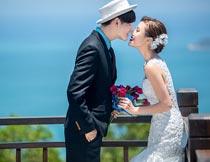 海边拿花束亲吻的幸福恋人摄影图片