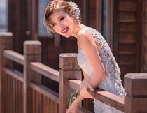 趴在栏杆上拿郁金香的新娘摄影图片