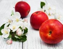 木板上的红苹果与花朵特写摄影图片