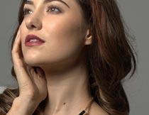 手摸脸颊戴项链的性感美女摄影图片