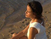 蹲在沙滩上看海的美女模特摄影图片