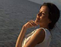 撑着下巴看海的性感美女摄影图片