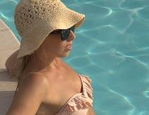 坐泳池里戴帽子墨镜的美女摄影图片