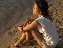 抱双腿坐沙滩上看海的美女摄影图片