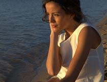 摸脸颊抱腿坐沙滩上的美女摄影图片