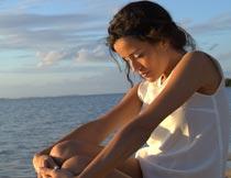 低头抱双腿坐沙滩上的美女摄影图片