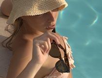 戴遮阳帽拿墨镜的泳装美女摄影图片