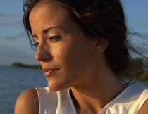 海滩边抱着肩膀的美女模特摄影图片