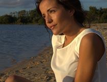 阳光下坐沙滩上的美女模特摄影图片