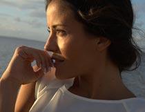 海边手摸嘴唇的美女局部摄影图片