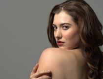 抱肩膀扭头的卷发红唇美女摄影图片