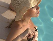 泳池里拿太阳镜的性感美女摄影图片