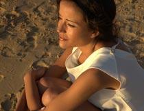 抱双腿坐沙滩上的美女模特摄影图片