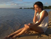 抱腿坐在沙滩上看海的美女摄影图片
