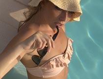 戴帽子拿太阳镜的泳装美女摄影图片