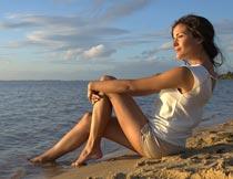 黄昏坐沙滩上看海的美女摄影图片