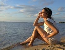坐在沙滩上的美女模特侧面摄影图片