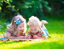 趴在草坪上看书的男孩女孩摄影图片