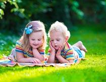 草地上撑着下巴看书的孩子摄影图片