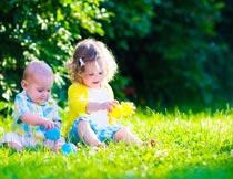 坐在草地上玩耍的男孩女孩摄影图片