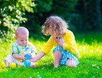 公园里坐草地上玩球的儿童摄影图片