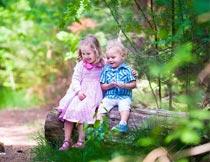 坐在木头上快乐的男孩女孩摄影图片