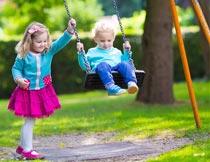 公园里开心荡秋千的儿童摄影图片