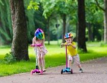 公园道路上玩滑板车的孩子摄影图片