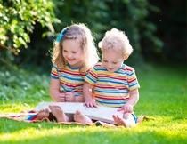 坐草地上开心看书的孩子摄影图片