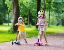 道路上快乐玩滑板车的孩子摄影图片