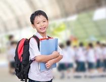 背着书包抱着书本的男孩子摄影图片