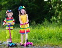 草地上开心玩滑板车的孩子摄影图片