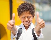 微笑着双手竖大拇指的男孩摄影图片