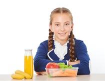 坐桌前的女孩与水果果汁摄影图片