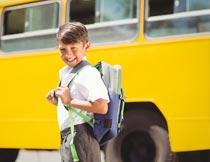 站校车前背书包的快乐男孩摄影图片