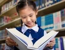 书柜前微笑看书的可爱女孩摄影图片