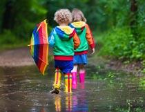 林间水坑里拿着雨伞的孩子摄影图片