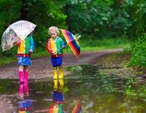 拿着雨伞走在水坑里的孩子摄影图片