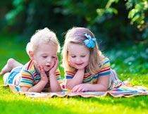 趴草地上撑着下巴的孩子摄影图片