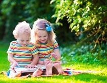 坐在草坪上看书的男孩女孩摄影图片